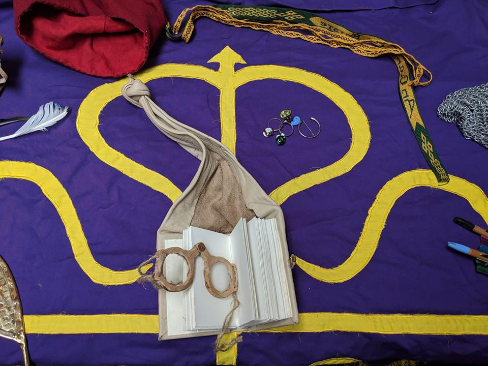 Various Arts and Sciences projects displayed on top of a Calontir Banner with purple background and gold cross of Calatrava.