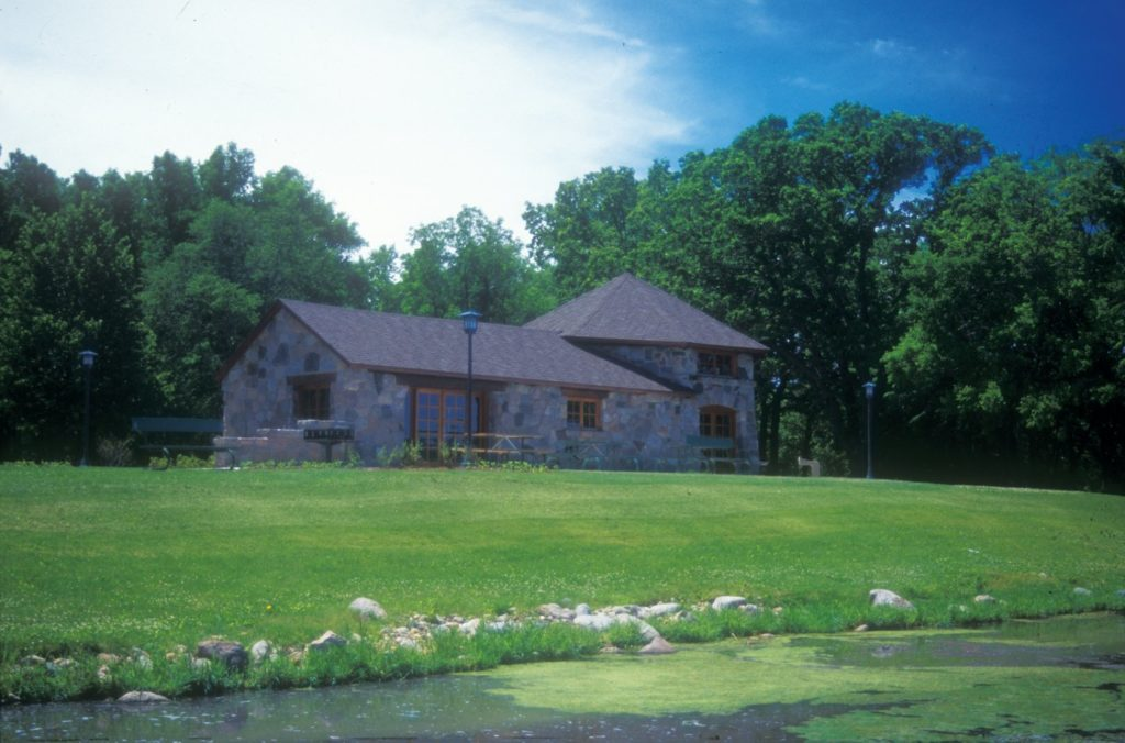 Rustic stone building with picnic tables, benches and grill outside viewed from the shore of the lake